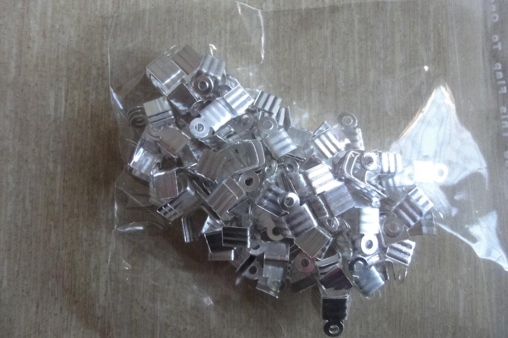 100 terminali fermafili zigrinati metallo color argento 7 mm.