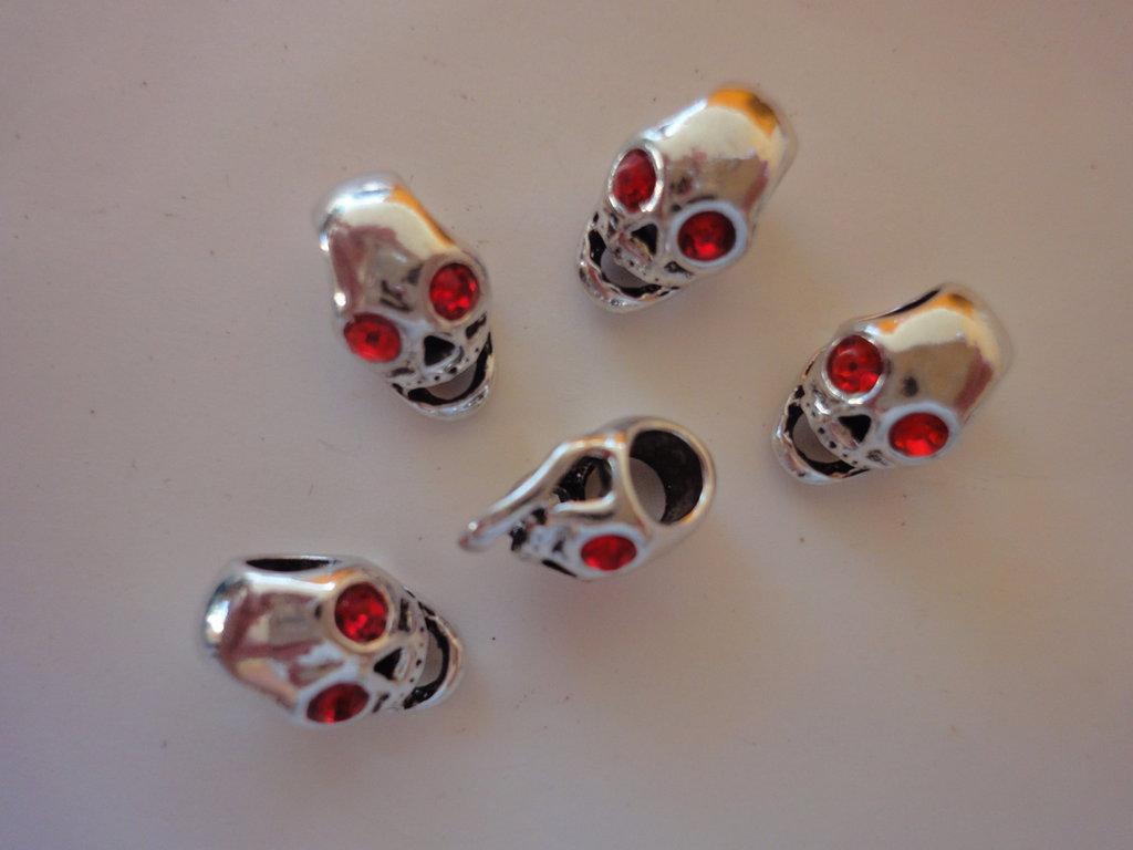 5 Perle teschio foro largo metallo lucido con occhi perle sfaccettate vetro rosso 14x9 mm.