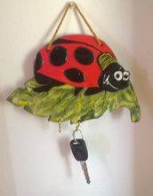 Portachiavi a forma di coccinella, rossa e nera, su foglia verde, di ceramica con elementi in rilievo.