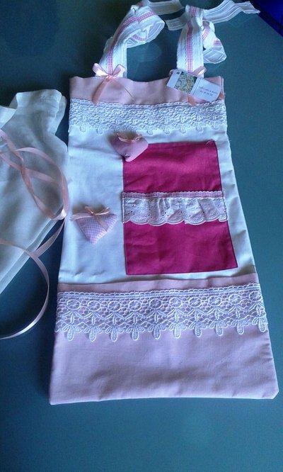 Porta oggetti e pigiama bebè da parete in cotone e decorazioni fantasia.