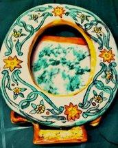 Cornice ovale di ceramica fatta a mano con motivi di arabeschi verde ramina e fiori arancio e giallo