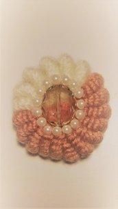 Spilla in lana realizzata ad uncinetto con filato color panna e giallo oro con cristallo centrale impreziosito da mezze perline
