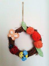 Ghirlanda fuoriporta con base tonda  in vimini con rose in cotone e decorazioni in polvere di ceramica