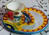 Piatto rotondo aperto da un lato, modellato a mano con tazza colazione di ceramica decorata