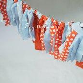 Ghirlanda di nastri di stoffa celesti e arancioni per decorare il tavolo della vostra festa a tema circo