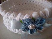 Un accessorio per il bebè-Cestino realizzato a uncinetto con fettuccia bianca e decorato con fiorellino celeste  perla e fiocco di raso