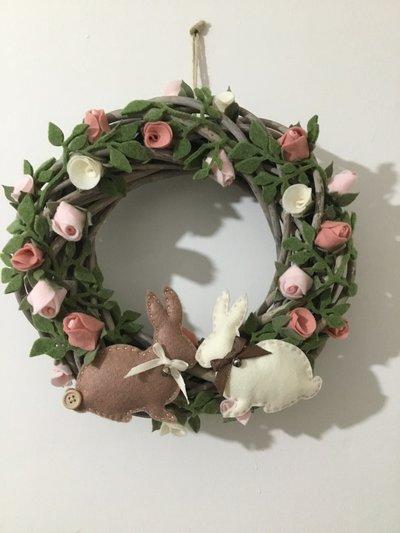 Ghirlanda fuoriporta con rose e coniglietti.