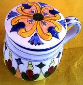 Tisaniera di ceramica vivacemente colorata su fondo bianco formata da tazza colino e tappo