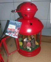 Presepe artigianale in lanterna rossa.