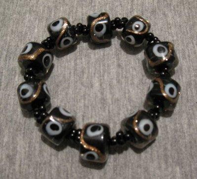 Bracciale elastico con perle in vetro nere a 'occhi'