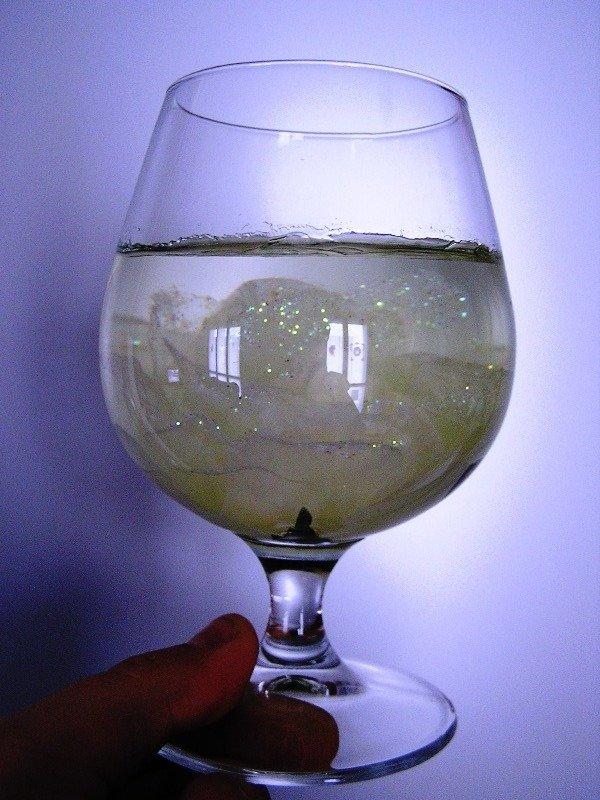 Bicchiere con fiore e cera liquida