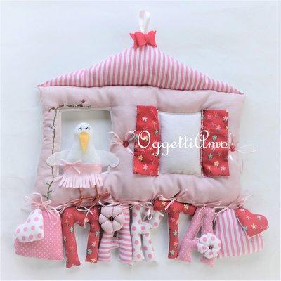 Un fiocco nascita per la piccola Marta: una targa composta da lettere imbottite per comporre il suo nome, una cicogna ed una cornice di tela aida per decorare la sua cameretta