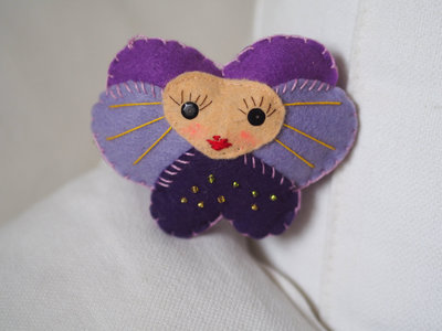 Spilla.Violetta imbottita con viso di donna.Feltro.Imbottita.Toni del lilla/viola.Paillettes,perline,ricami aggiunti.Spilla o nastro-raso.