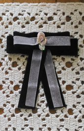 Spilla con fiocco realizzata con nastro in velluto nero ed organza rosa ed elemento bijoux centrale
