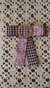 Spilla con fiocco realizzata con nastro grosgrain a quadri rosa e nero inserti in pizzo ed elemento bijoux centrale