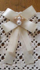 Spilla con fiocco realizzata con nastro in raso panna ed elemento bijoux centrale