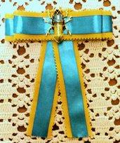 Spilla con fiocco realizzata con nastro gros-grain giallo senape e in raso turchese ed elemento bijoux centrale