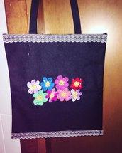 Borsa in tessuto decorata con fiori a uncinetto