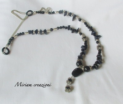 Collana lunga con perle nere ed elementi argentati.