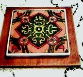 Sotto pentola o piccolo quadro di terracotta rossa, incollata su legno lucidata con motivi di vario colore