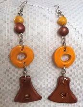 2 Palline e 2 pendente  nei colori bronzo e giallo sole di ceramica  con monachelle al lobo dell'orecchio