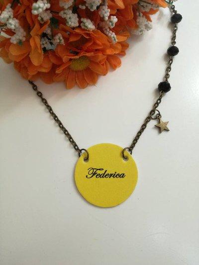 Collana nome con ciondolo di carta a cerchio di colore giallo, catenina bronzo e perline nere.