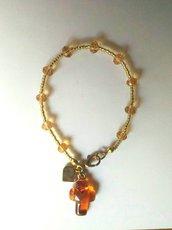 Braccialetto rosario in rocailles dorate e mezzi cristalli ambrato con crocifisso in vetro di Murano