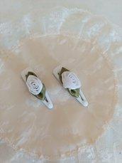 Delicata coppia di fermaglietti con roselline di raso bianco e foglioline verdi.