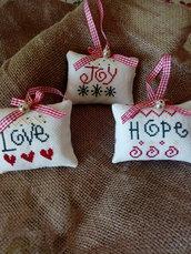 Decorazioni natalizie a forma di cuscino con messaggi ricamati con punto croce.
