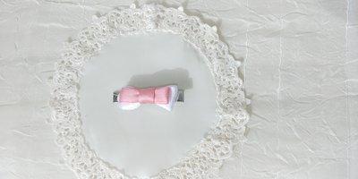 Fermaglietto da bambina a forma di molletta decorato con fiocchetto di raso bianco e con un'altro fiocchetto rosa sovrapposto.