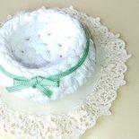 Bomboniera a forma di ciotolina realizzata a punto canestro con fettuccia bianca e decorata con cordino verde chiaro in tutto il contorno e fiocchetto finale