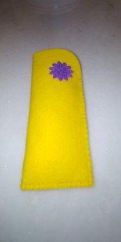 Portaocchiali di feltro di colore giallo cucito a mano e decorato con grazioso fiorellino di pannolenci di colore viola.