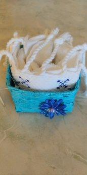 Cestino di vimini turchese decorato con delicato fiorellino blu con al centro una perla con all'interno  un piccolo asciugamano  di spugna con frangette e disegno tipo punto croce
