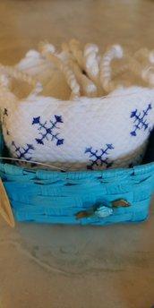 Cestino di vimini turchese decorato con delicato fiorellino in tinta contenente un piccolo asciugamano  di spugna con frangette e disegno tipo punto croce