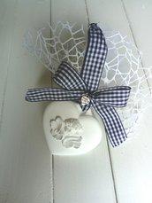 Bomboniera in polvere di ceramica a forma di cuore con angelo puttinoe medaglione con angelo della purezza.