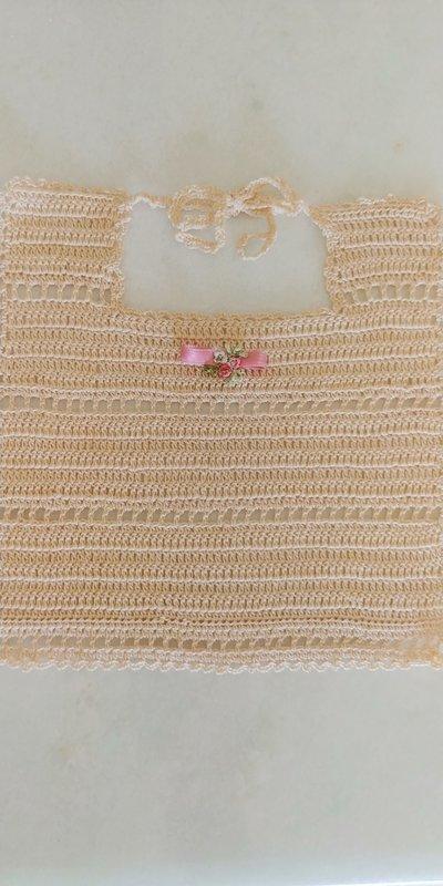 Bavaglino in filato di puro cotone di colore beige realizzato a uncinetto a punto alto e file di quadratini vuoti con  fiocchetto di raso rosa e fiorellini