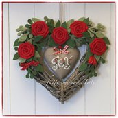 Cuore in vimini tinta naturale decorato con rose rosse, rametti verdi e cuore di lino grezzo con scritta joy