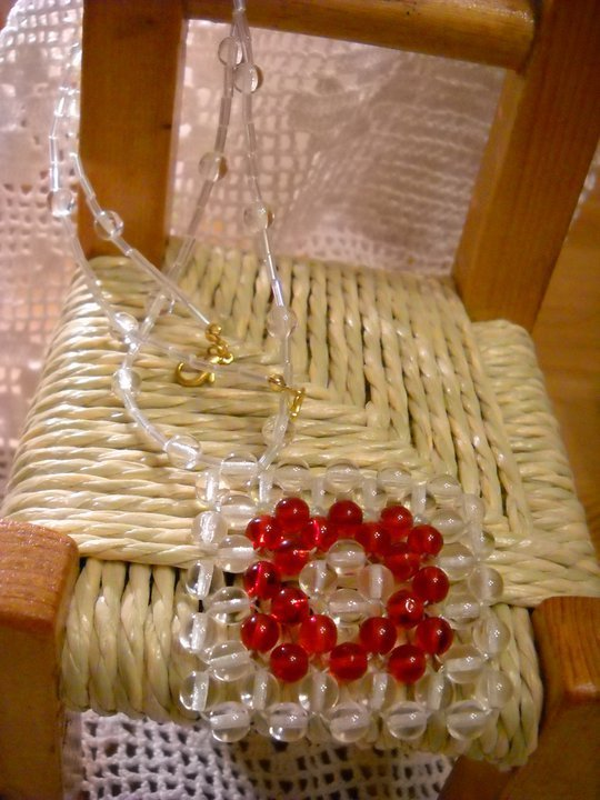 Collana con tubetti trasparenti e un ciondolo quadrato composto da perle di vetro trasparenti e rosse