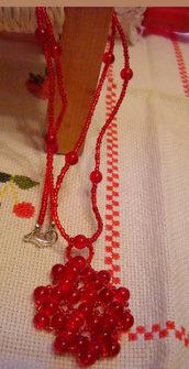 Collana con perline rosse e ciondolo con lavorazione a fiore