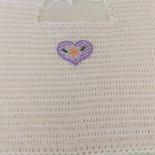Bavaglino per neonati realizzato a uncinetto con filo di scozia di colore bianco ed impreziosito da un cuoricino viola