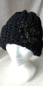 Elegante cappello di lana di colore nero realizzato a uncinetto con fiore nero e oro.