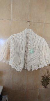 Ampia mantellina -coprispalle realizzata in lana di colore panna  con spilla a forma di fiore che orna e permettere di chiudere lamantellina