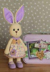 Coniglietta all'uncinetto con un romantico vestito di stoffa.
