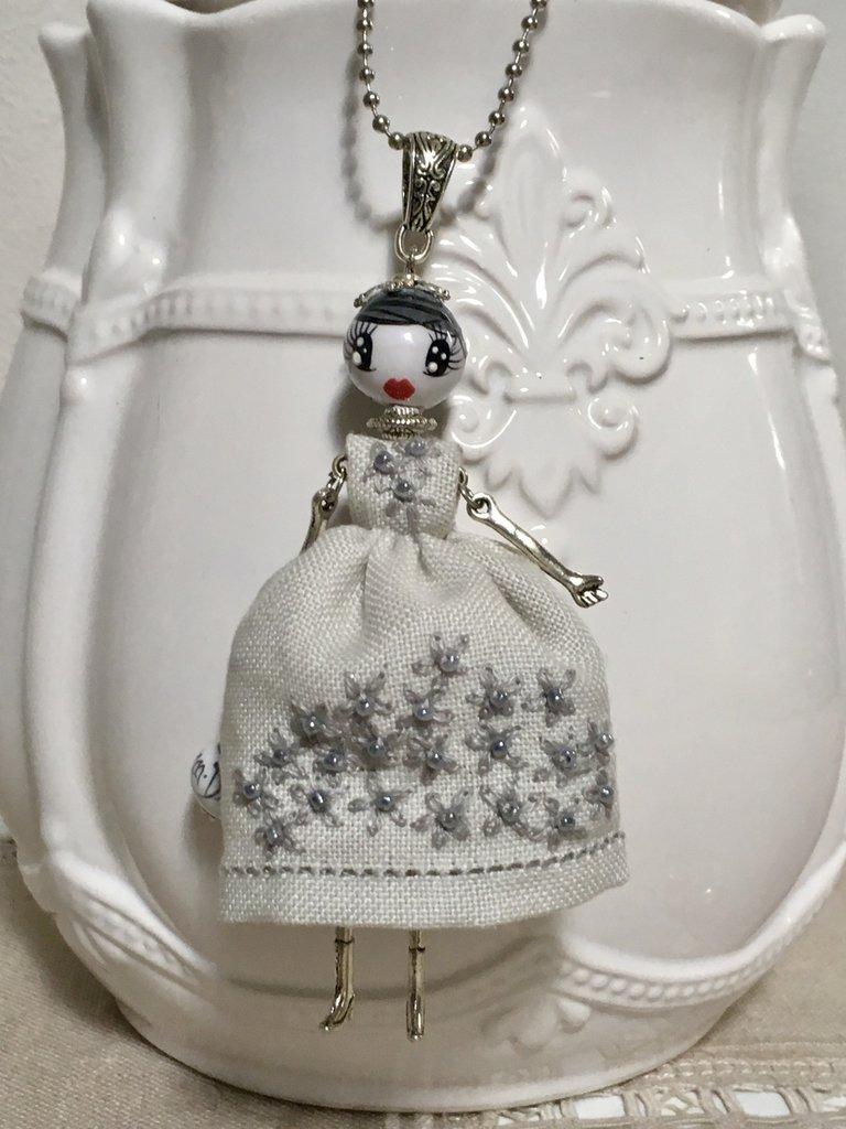 Collana lunga dolls di ceramica dipinta con vestito di lino grigio ricamato a mano.