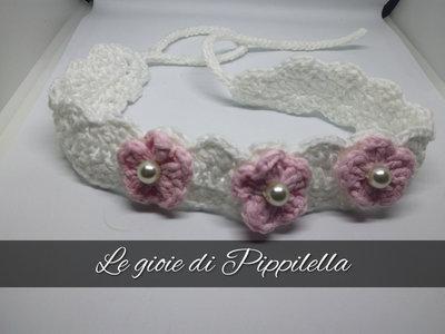 Fascia fermacapelli crochet bianca con fiori rosa e perle.
