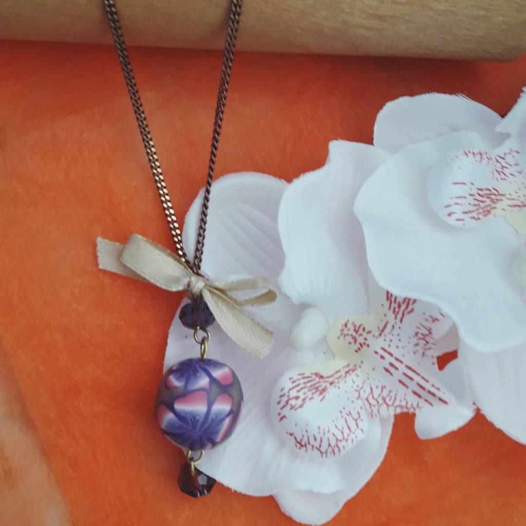 Ciondolo lungo pendaglio primaverile con perla floreale e fiocchetto