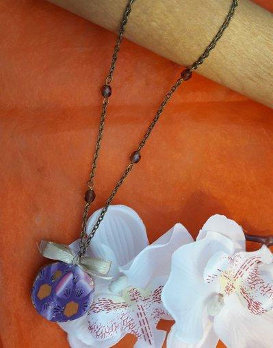 Ciondolo lungo tondo primaverile modellato a mano. Decorato con fiocchetto, catenella anticata e mezzi cristalli color topazio