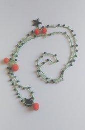 Collana lunga uncinetto con filato verde e mezzi cristalli verde scuro e verde acqua con piccoli charms stelline verdi in legno e pompons arancio
