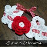Fascia fermacapelli crochet da bambina con fiore rosso.