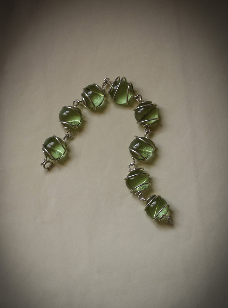 Bracciale perle vetro verde acqua incastonate su filo metallico argentato.